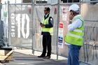 A security guard keeps watch on the closed Mainzeal construction site at Shed 10, Queens Wharf. Photo/ Michael Craig