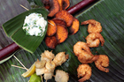 Sweet potato chips with coconut prawns, fish and banana kebabs. Photo / Doug Sherring