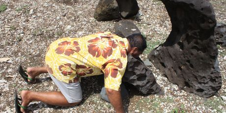 Rua Samuela demonstrates the headcutting stone at the 1000-year-old Paengaariki Marae on Aitutaki. Photo / Jim Eagles