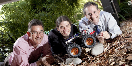 Richard Parker, Andre Geldenhuis and Chris Hann with the small UC rover robot designed to inspect floor piles of damaged buildings. Photo / Supplied
