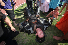 Charlie Tapsell lies exhausted after completing a 5km run around the track at Tauranga Domain in a full suit of authentic Medievil armour weighing 40kg. Photo / Bay of Plenty Times