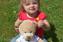 18-month-old Hayley Ryan with Nait, the travelling teddy bear who is currently staying with Hayley and her family in Stratford. Photo / Supplied