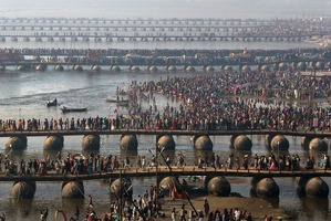 Hindu devotees walk across pontoon bridges to take a holy dip at Sangam, the confluence of the Ganges. Photo / AP