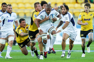 Peter Saili of the Blues is tackled by Brad Shields of the Hurricanes. Photo / Getty Images.