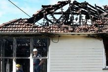 Police examine the Anzac Parade house that was gutted by a fierce fire on Saturday. Photo / Bevan Conley