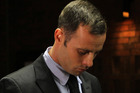 Olympic athlete Oscar Pistorius stands inside the court as a police officer looks on during his bail hearing at the magistrate court in Pretoria, South Africa. Photo / AP
