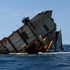 The wreck of the MV Rena with a salvage barge behind. Photo / Alan Gibson