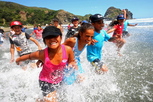 From left, Victoria Faasavalu, Chance Morgan and Sione Niupalau, all 10, enjoying the Piha surf. Photo / Chris Gorman