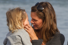 Meg Strange, the wife of shark victim Adam Strange, with daughter Indigo, 2, at Muriwai Beach. Photo / Brett Phibbs