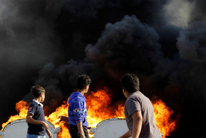 Bahraini boys look at an anti-government protester, unseen, as he adds fuel to old furniture being set on fire in a street in Malkiya, Bahrain. Photo / AP