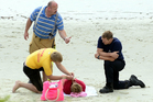A lifeguard helps a rescued swimmer. Photo / Otago Daily Times