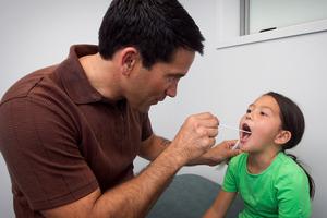 Dr Lance O'Sullivan swabs 7-year-old Raukura McNab's throat.  Photo / Natalie Slade