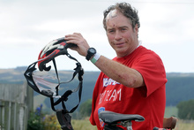 John Nicholl with what is left of his helmet and his damaged bicycle. Photo / Supplied