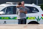 A person is consoled at the scene at Morningside Road crossing. Photo / Brett Phibbs