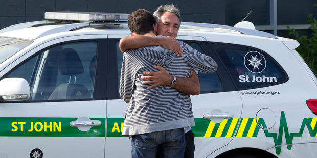 Loading A person is consoled at the scene at Morningside Road crossing. Photo / Brett Phibbs
