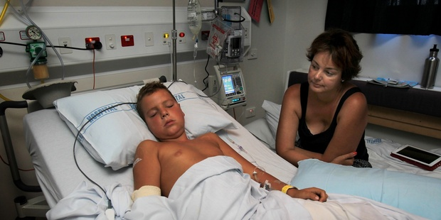 Marcus Carlyle, 8, and mum Jodie in Tauranga Hospital, after Marcus's leg was impaled by a large branch when he fell off his motorbike. Photo / Bay of Plenty Times
