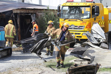 Firefighters remove roofing material from a storage shed complex which was gutted by a fire. Photo / Geoff Sloan