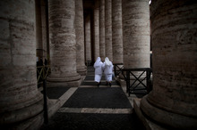 Two nuns walk under the Bernini colonnade at the Vatican, where cardinals will gather as early as this week to elect a new Pope.  Photo / AP