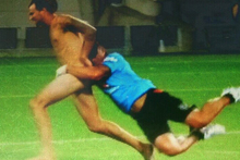 The Warriors strength and conditioning coach Ruben Wiki tackles a streaker at halftime in the Warriors pre-season match with the Broncos. Photo / Vodafone Warriors Facebook.