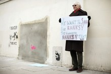 A man holds a placard during a protest next to a section of a wall where Banksy's Slave Labour graffiti artwork was removed in north London.Photo / AFP 