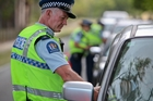 PUT TO TEST: Sergeant Ray Kirkby, from Hawke's Bay Road Policing, breath-tests a driver at a checkpoint on Waimarama Rd near Red Bridge yesterday. PHOTO/GLENN TAYLOR HBT134420-01
