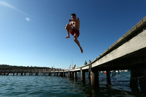 A man jumps into the water at Balmoral Beach, Sydney to cool off during a record hot day in October. Photo / Getty