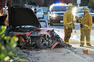 Firefighters stand near the wreckage of the Porsche that hit a light pole, killing actor Paul Walker and his friend Roger Rodas. Photo / AP
