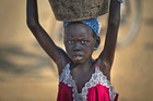 A young displaced girl carries a bucket of water back to her makeshift shelter at a UN compound which has become home to thousands of people displaced by the recent fighting. Photo / AP