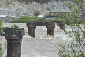 The Grey River rages around the old piles for the Cobden Bridge at Greymouth. Photo / Greymouth Star