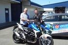 Mike Winks (left), Suzuki NZ motorcycle rep, hands winning early bird ticket holder Alastair Kidd the keys to a new GSR 750. Photo/Supplied