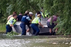Police and survivors recover a jetboat that crashed, killing one and injuring four others. Photo / John Cowpland