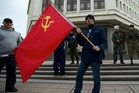 A resident of Simferopol in Ukraine's Crimea region shows his support for Russia by holding the country's flag outside the local parliament buildings yesterday. Photo / AP