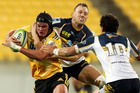 Adam Hill of the Hurricanes is tackled by Jesse Mogg of the Brumbies. Photo / Getty Images