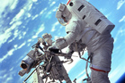Astronaut Steven L. Smith, payload commander, retrieves a power tool while standing on the mobile foot restraint at the end of the remote manipulator system. Photo / NASA