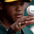 Oakland Athletics shortstop Addison Russell rolls a baseball on his hand in the dugout as the Athletics play the Arizona Diamondbacks in an exhibition spring training baseball game. Photo / AP