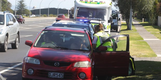 A woman gets attended to by St Johns staff after a crash on Maunganui Rd.  Photo: John Borren