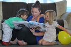 Porse nanny intern Ashley Presland keeps Chloe, 1, and Dani Hudson, 3, amused. Photo/John Borren