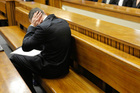 Oscar Pistorius blocks his ears inside the High Court on the second day of his trial in Pretoria. Photo / AP