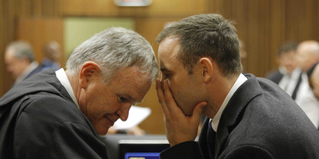 Oscar Pistorius, talks with his attorney, Barry Roux, left, inside court on the second day of his trial. Photo / AP
