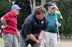 Tararua's Mark Thomson putts as the Waitara pairing of Ross Jenkins (left) and Roy Frost watch at the Hawke's Bay Golf Club yesterday.