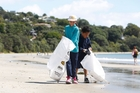 Mercy Kiddie, left, and Sam Tuimauga, from Dawson Primary, fill up their bags with beach litter. Photo / Chris Gorman