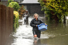 Residents in Shirley move their belongings out of their flooded homes in Christchurch, New Zealand. Photo / Martin Hunter