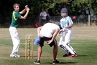 Umpire Paul O'Callaghan has to get low as the ball evades Wanganui High School bowler Dylan Martin, while Cullinane College batsman Raymond Teki looks on. Photo/Bevan Conley