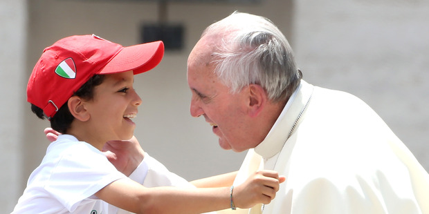 Pope Francis embraces a boy in St. Peter's Square at the end of his weekly audience. Photo / Getty Images