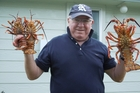Television presenter Keith Quinn holds up some crayfish at his holiday home in the Wairarapa.
