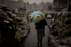 A woman walks past barricades set up by anti-Yanukovych protesters at Kiev's Independence Square, in Ukraine. Photo / AP