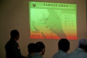 Indonesian Air Force officers examine the projection of a map that shows their operation area over the Strait of Malacca. Photo / AP