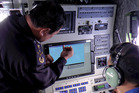 Malaysian Maritime Enforcement Agency chief Admiral Mohd Amdan Kurish discusses the search with a radar operator. Photo / AP