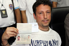 Italian Luigi Maraldi, whose stolen passport was used by a passenger boarding a missing Malaysian airliner, shows his passport as he reports himself to Thai police at Phuket police station. Photo / AP