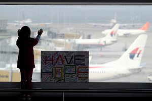 A girl stands next to a sign board made and written by the public at Kuala Lumpur International Airport. Photo / AP